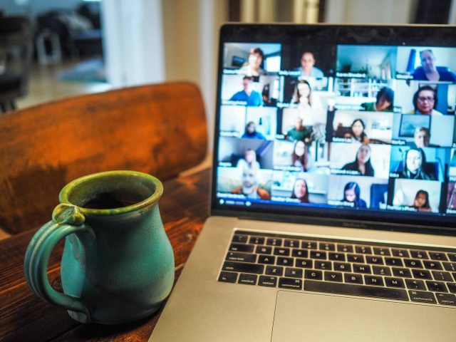 Mug next to a laptop showing Zoom call.