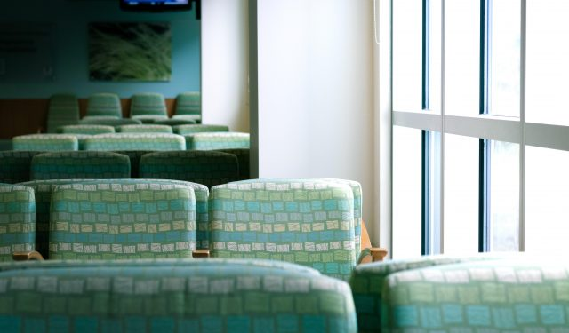 Empty green chairs of a waiting room next to a bright window